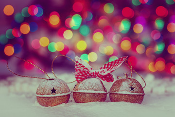 Greeting Christmas Card with Gold Jingle Bells on Colorful Bokeh Background. Toning image.