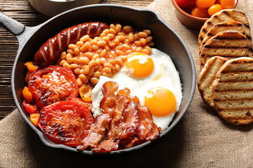 English Breakfast with sausages, grilled tomatoes, egg, bacon and beans on frying pan.