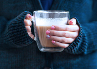 The girl in the blue sweater holding a transparent cup of coffee. Women's hands. beautiful pink manicure. concept autumn