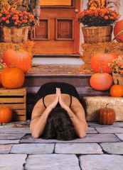 beautiful lady doing yoga pose on fall backdrop