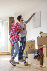 Young couple in new flat, he is positioning frame of picture on the wall while she looking leaning on the broom with unpacked boxes on background