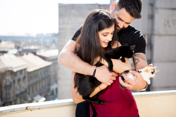 Young couple holding cats in hands on the terrace. Relax and love. Animal care. Animal lovers