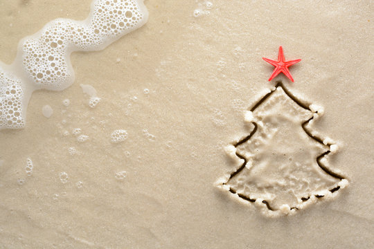 Holiday background - Christmas tree with starfish drawn on a sandy beach
