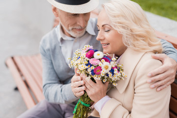 Two pensioners are sitting on a bench in the alley. The aged man gave the woman flowers. He holds her hand
