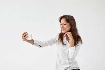Charming happy young woman employee wearing formal white blouse taking selfie on smart phone, smiling broadly at camera, showing her perfect teeth, having small break while working at office