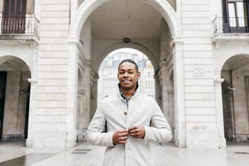 Trendy black man posing cheerfully at street