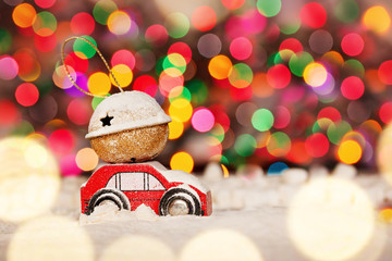 Miniature Red Car Carrying a Gift on roof on colorful bokeh background.
