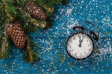 Image of Christmas branches of spruce, cones and clocks, snow