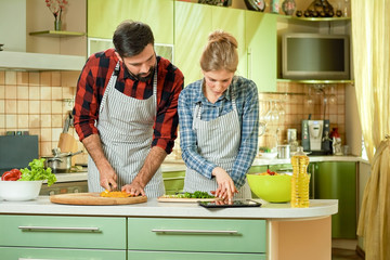 Couple with tablet cooking. Woman and man, vegetables. Find recipes in the internet.