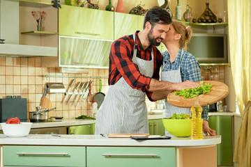 Woman kissing man, kitchen. Cheerful guy preparing food. Home cooking health benefits.