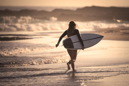 Female surfer running on the beach with her surfboard