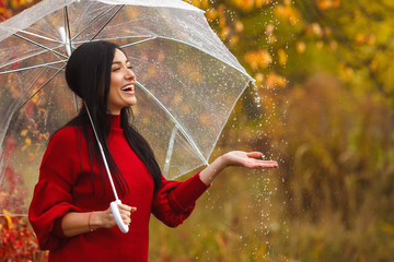 Beautiful woman holding umbrella in the rain and smiling. Autumn background. Cheerful young girl having fun at the rain in the fall time.