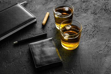 Man set. Whiskey with ice, cigar, wallet and notebook black bar background