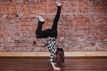 Breakdance is life. Happiness in moving. Sporty teenage girl, brick wall background with free space. Hip hop lifestyle, flexible dancing young female, movement concept