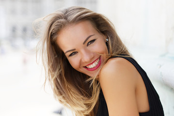 Happy young carefree woman smiling outdoor portrait