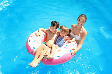 Young woman and her children with inflatable donut in swimming pool