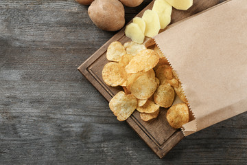 Board with crispy potato chips on wooden table