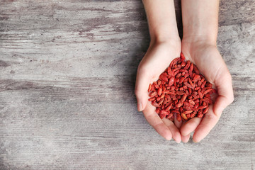 Hands of woman holding red dried goji berries on wooden background