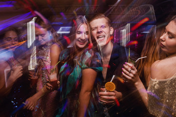 Happy company dancing in motion. Joyful New Year in night club, active Christmas celebration. Disco party with alcoholic drinks in blurred colors, modern youth life