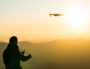 Silhouette of young man using drone at sunset for photos and video making - Happy man having fun with new technology trends in mountains