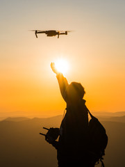 Silhouette of young man catching drone at sunset for photos and video making - Happy man having fun with new technology trends in mountains