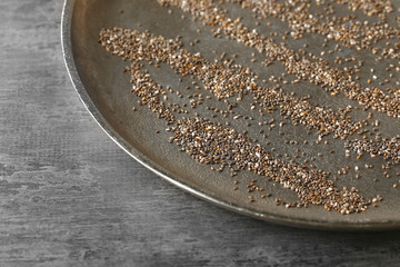 Plate with scattered chia seeds on table, closeup