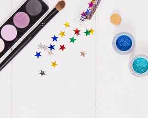 Decorative flat lay composition with makeup products, cosmetics and glass jars with decorative multi-colored stars. Flat lay, top view on white wooden background. Concept Chrismas, New years make-up .