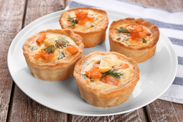 Plate with tasty salmon tartlets on table