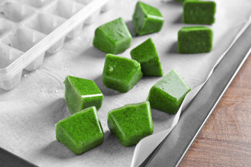 Frozen vegetable puree and ice tray on paper