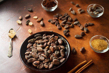 Raw cocoa beans, cacao powder and brown sugar on dark stone background