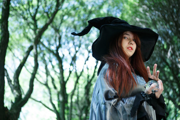 Picture of young witch in gloomy forest