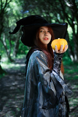 Photo of young witch with pumpkin