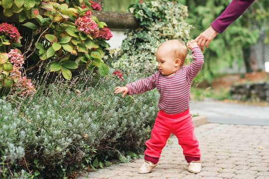 Adorable baby girl of 9-12 months old playing outside, wearing pink body and joggers, holding mother's hand. Child's first steps, kid learning to walk