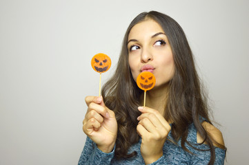 Young beautiful woman with halloween lollipops. Studio picture isolated on gray background.