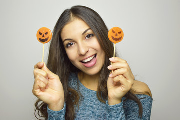Young beautiful smiling woman with halloween lollipops. Studio picture isolated on gray background.