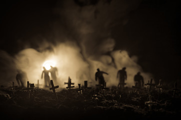 Silhouette of zombies walking over cemetery in night. Horror Halloween concept of group of zombies at night Wall mural