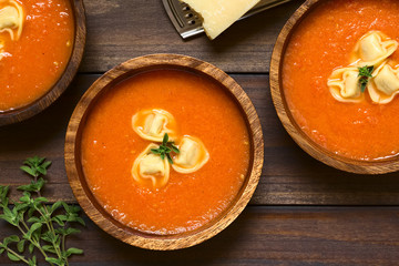 Homemade fresh cream of tomato soup with tortellini garnished with fresh oregano, served in wooden bowls, photographed overhead on dark wood with natural light