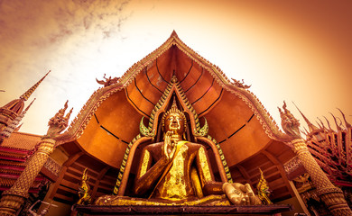 """Golden Buddha statue decorated with mosaic inside the semi-circular dome named """"Chin Prathanporn"""" situated in outdoor area of Wat Tham Sua(Tiger Cave Temple),Tha Muang District,Kanchanaburi,Thailand."""