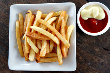 French fries and tomato sauce In the dish on a wooden table.