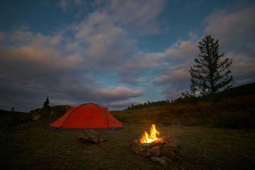 A tent and campfire under an evening sky
