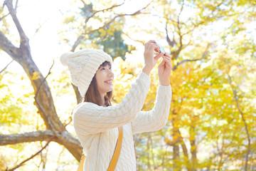 紅葉をスマートフォンで撮る女性