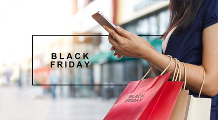 Black Friday, Woman using smartphone and carrying shopping bag while standing on the mall background
