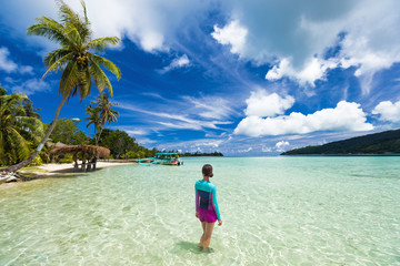 Wall Mural - Beach vacation tourist woman swimming in French Polynesia island on cruise excursion at Huahine paradise motu. Tahiti travel holiday. Girl wearing sun protection clothing rashguard for solar skincare.