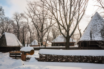 Traditional homestead covered in snow at the Village Museum in Bucharest, Romania