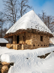 A stone cottage with a thatched roof covered in snow