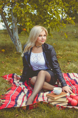 Middle age stylish blonde hair pretty woman dressed in leather black jacket on a cozy picnic in autumn garden with philosophical mood. Lady with pretty accessorize and casual style on a nature