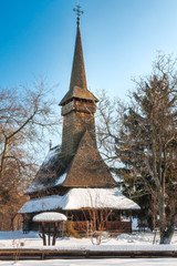 Traditional Romanian wooden Church covered in snow at Village Museum in Bucharest