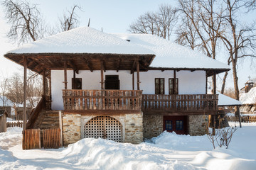 Front view of an old traditional Romanian house in winter.