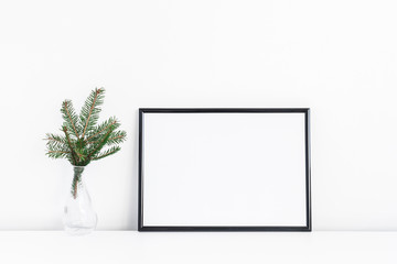 Christmas composition. Black frame and christmas tre branches on white background. Front view, mock up, copy space