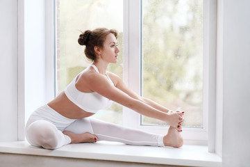 Woman doing yoga asana on window sill
